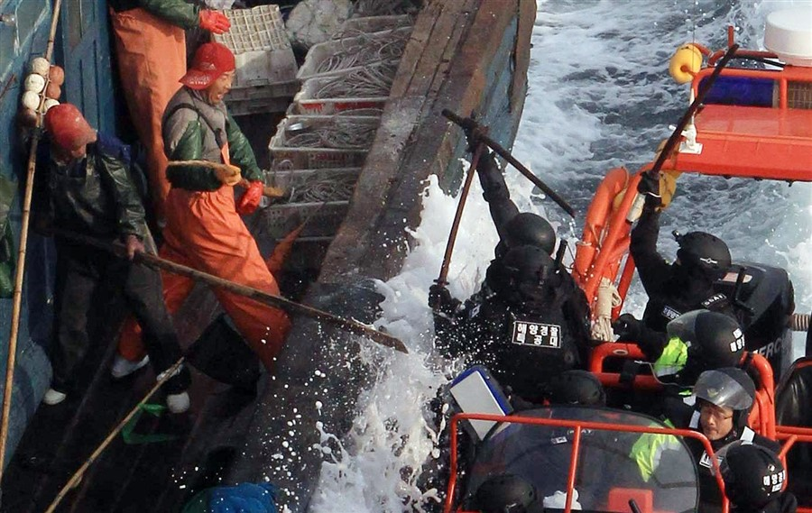 Chinese fishermen fight to stop South Korean Coast Guard agents from boarding during a crackdown on alleged illegal fishing in the Yellow Sea. Photo: Dong-a Ilbo, Getty Images